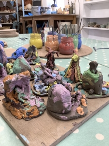 selection of modeled clay painted with glazes, create by children with glazes in the background