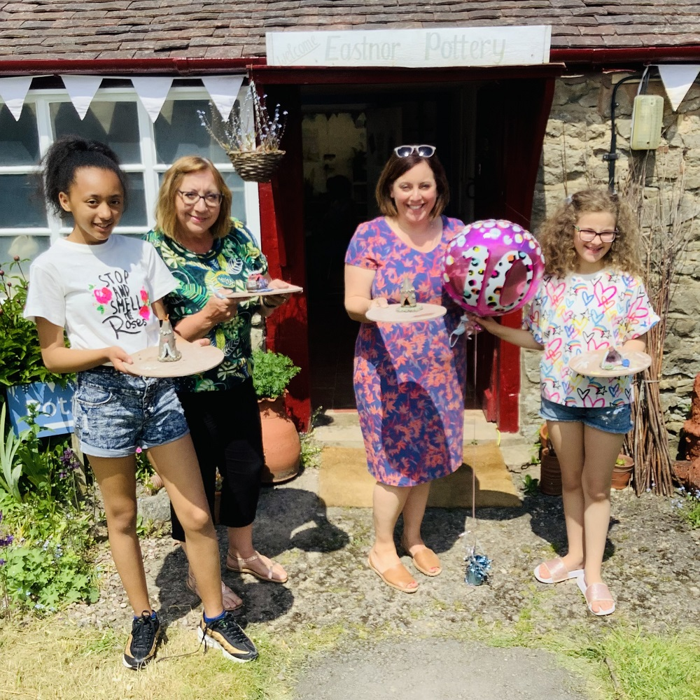 2 adults and 2 children stood outside pottery holiding 10th birthday baloon and trays with their clay creations made at eastnor pottery