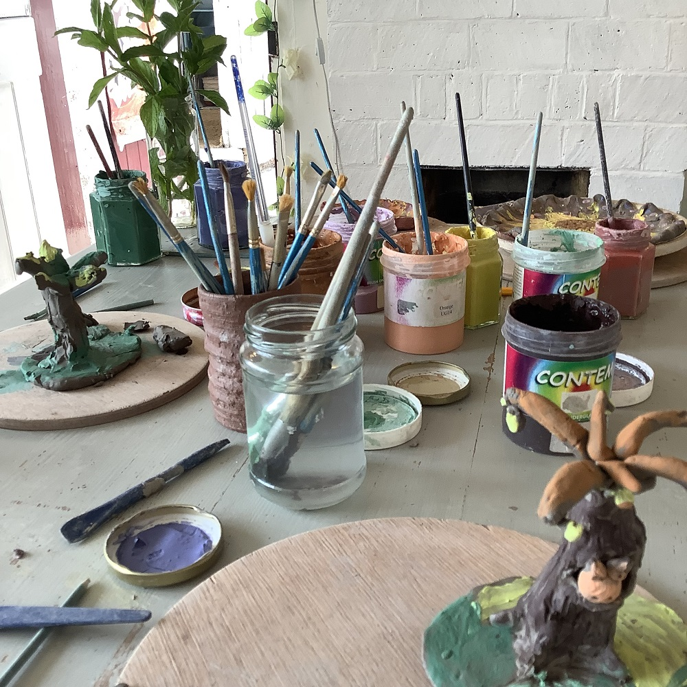 table with pots of glazes and water with paintbrushes inside after a clay modelling session