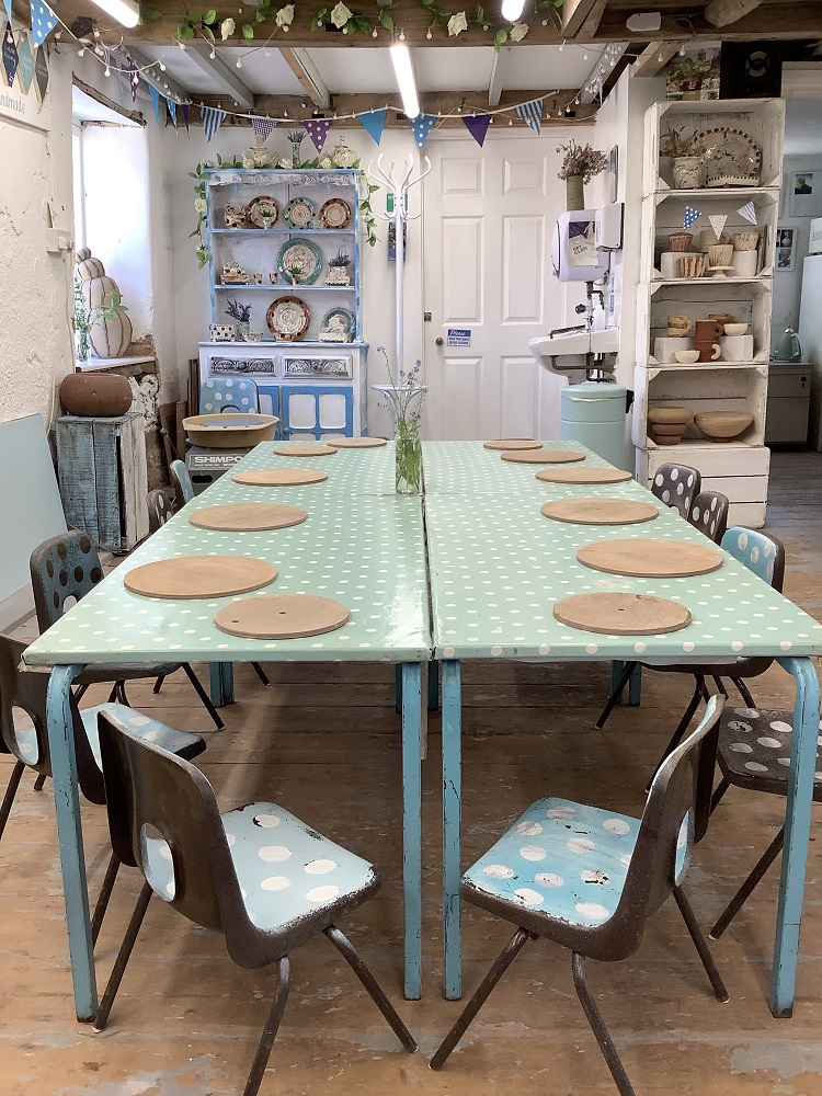 table with round wooden boards and children's chairs surrounding ready for a clay modelling session