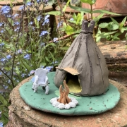 clay hand modeled tepee with green base, fire and white chair