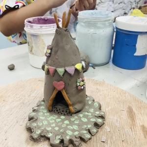 clay hand modeled tepee surrounded with multicoloured bunting and red heart on top of door with a green base