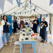 6 women standing round a table inside a marquee wearing aprons and holding wooden boards with hand modeled clay