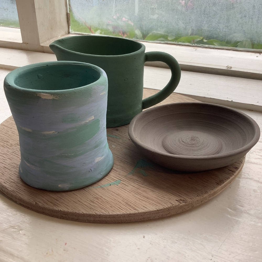 a green jug, green and purple pot and an unpainted ceramic dish on a wooden board