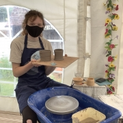 lady with a mask on sat at a potters wheel holding up wooden board containing 2 pots she has thrown