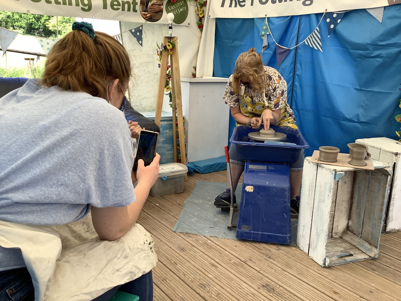 daughter filming mother on her phone whilst throwing a pot on a potters wheel