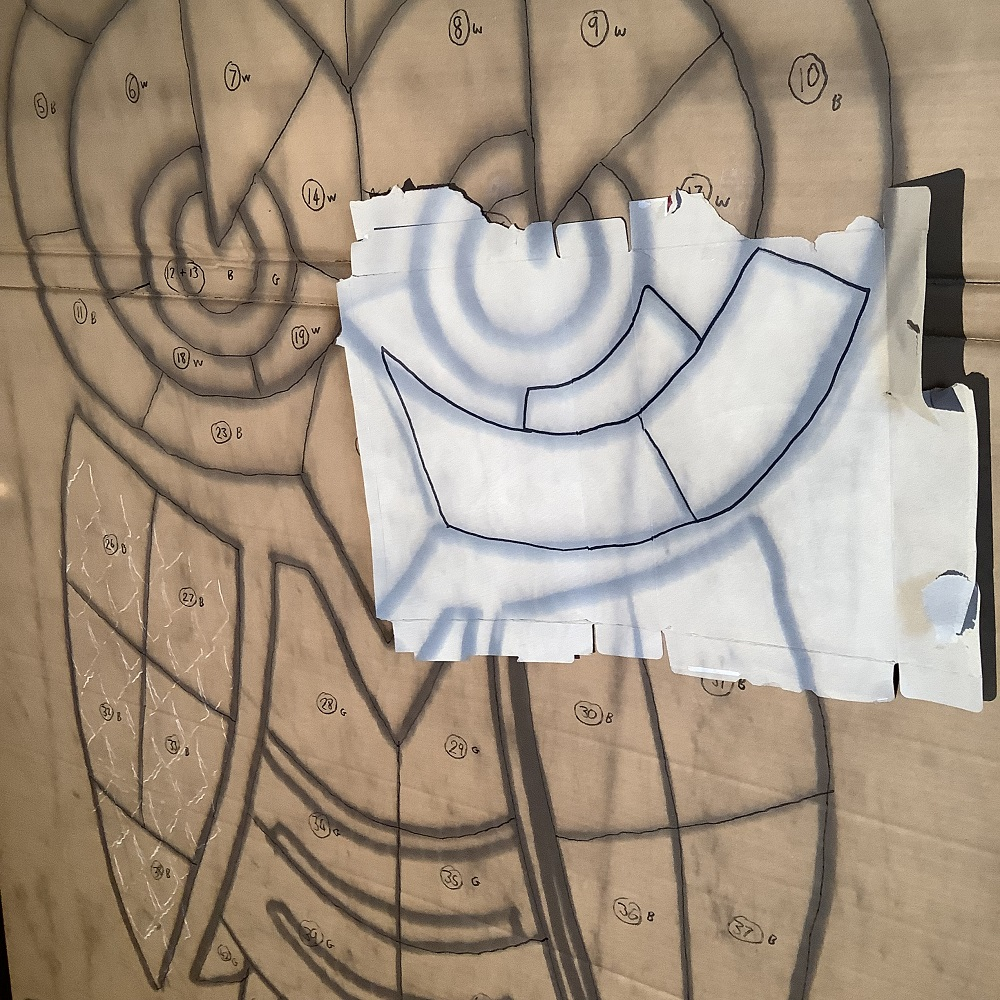 owl drawing in segments projected on to wooden board with measurement tracing paper on top