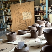 owl drawing in degments projected on to wooden board, with clay pots in the foreground
