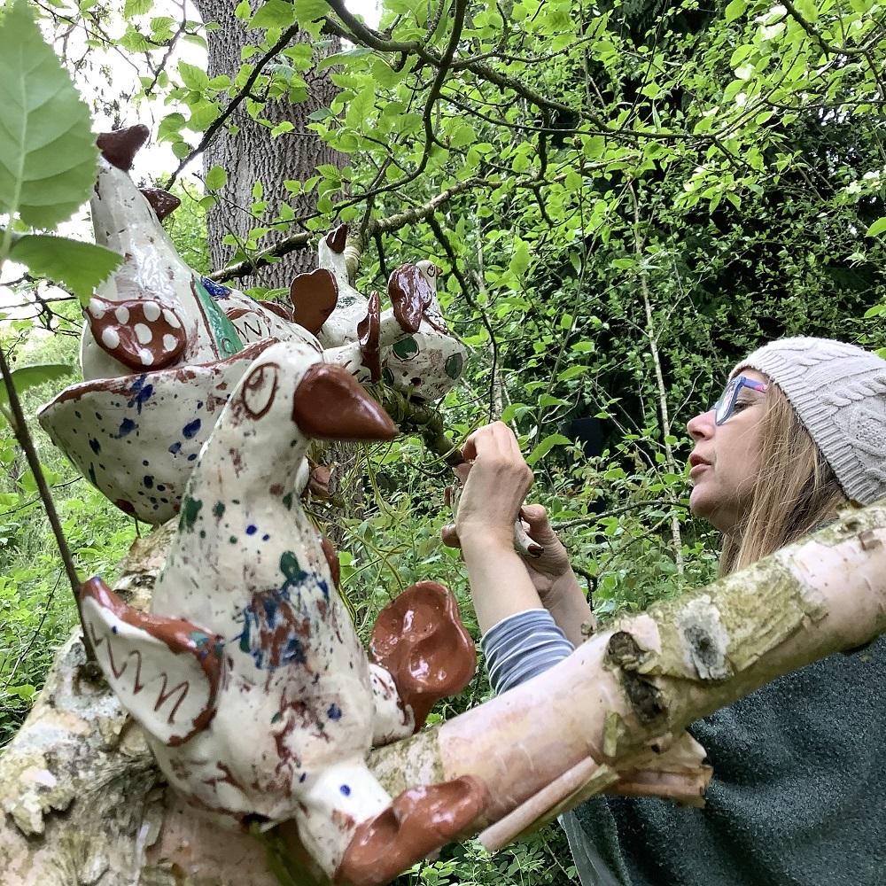 potter Sarah Monk placing ceramic birds in the trees of hellens gardens