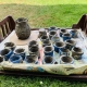 plastic tray holding coil clay pots painted blue and a larger pot decorated with 3D faces