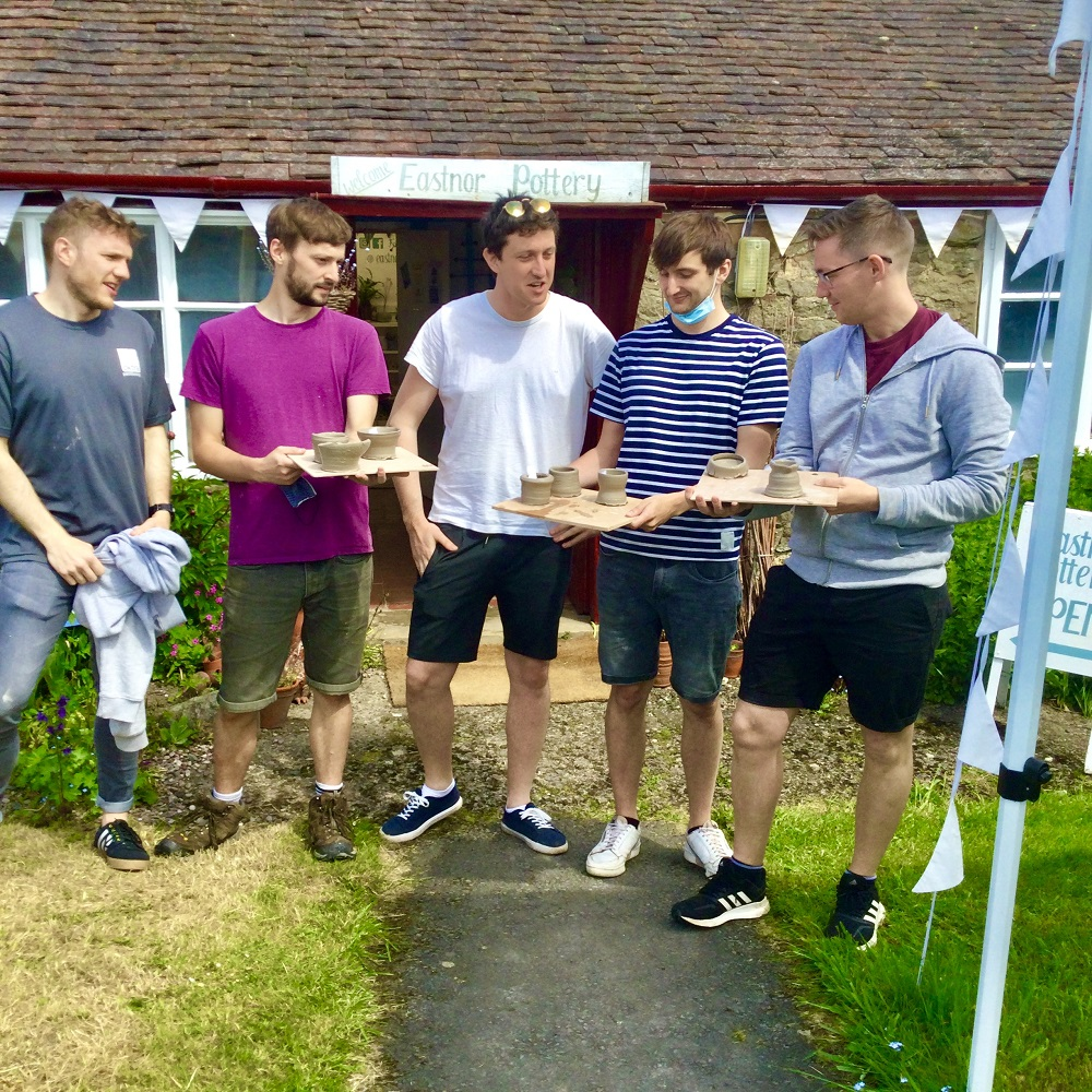 5 men stood outside eastnor pottery hold pots made on introductory session