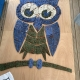 blue white and green tiles hand modeled with clay which together make up an owl