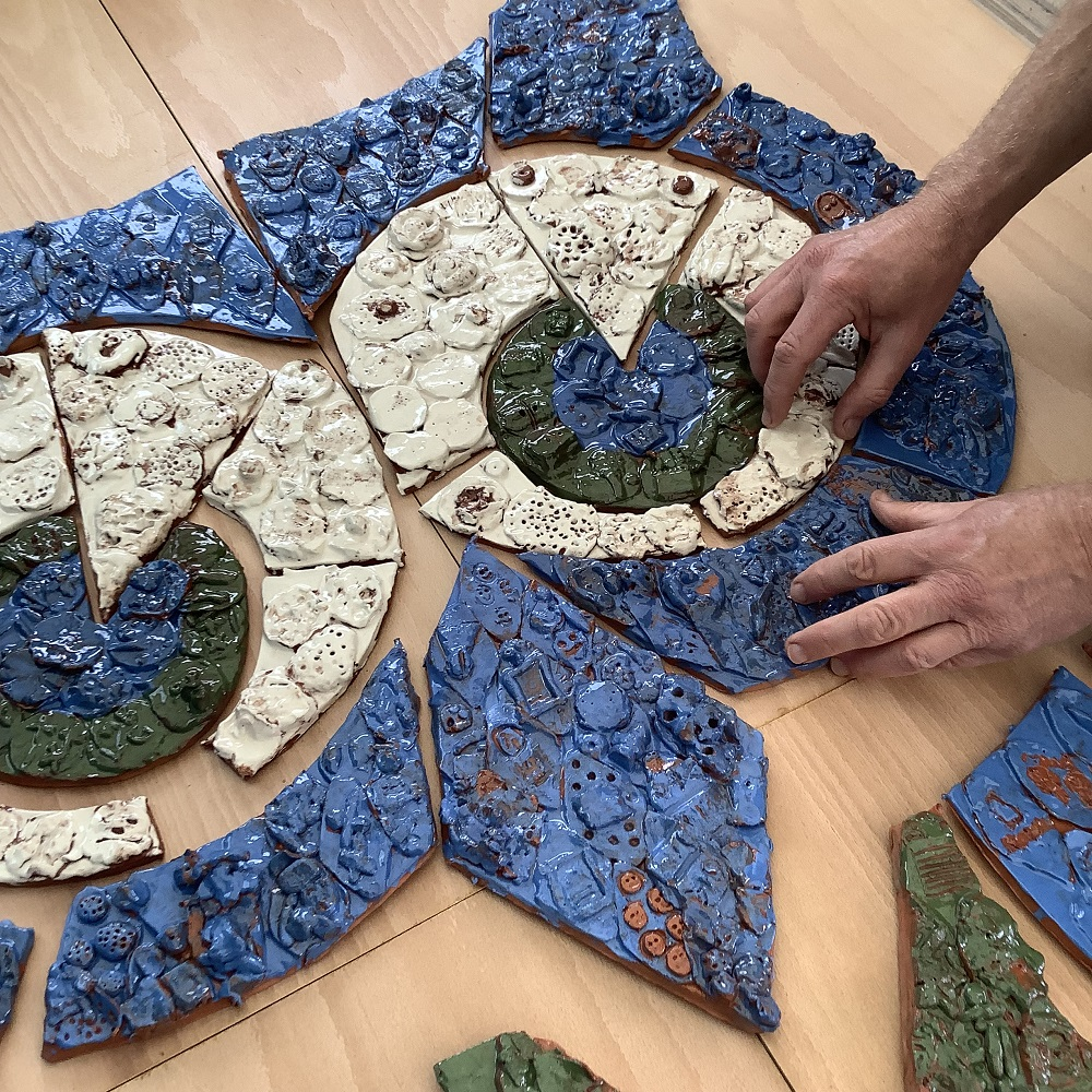 blue white and green tiles hand modeled with clay which together make up an owls face