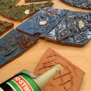 terracotta tiles painted blue and green with a glue gun tip in corner and glue on wooden surface