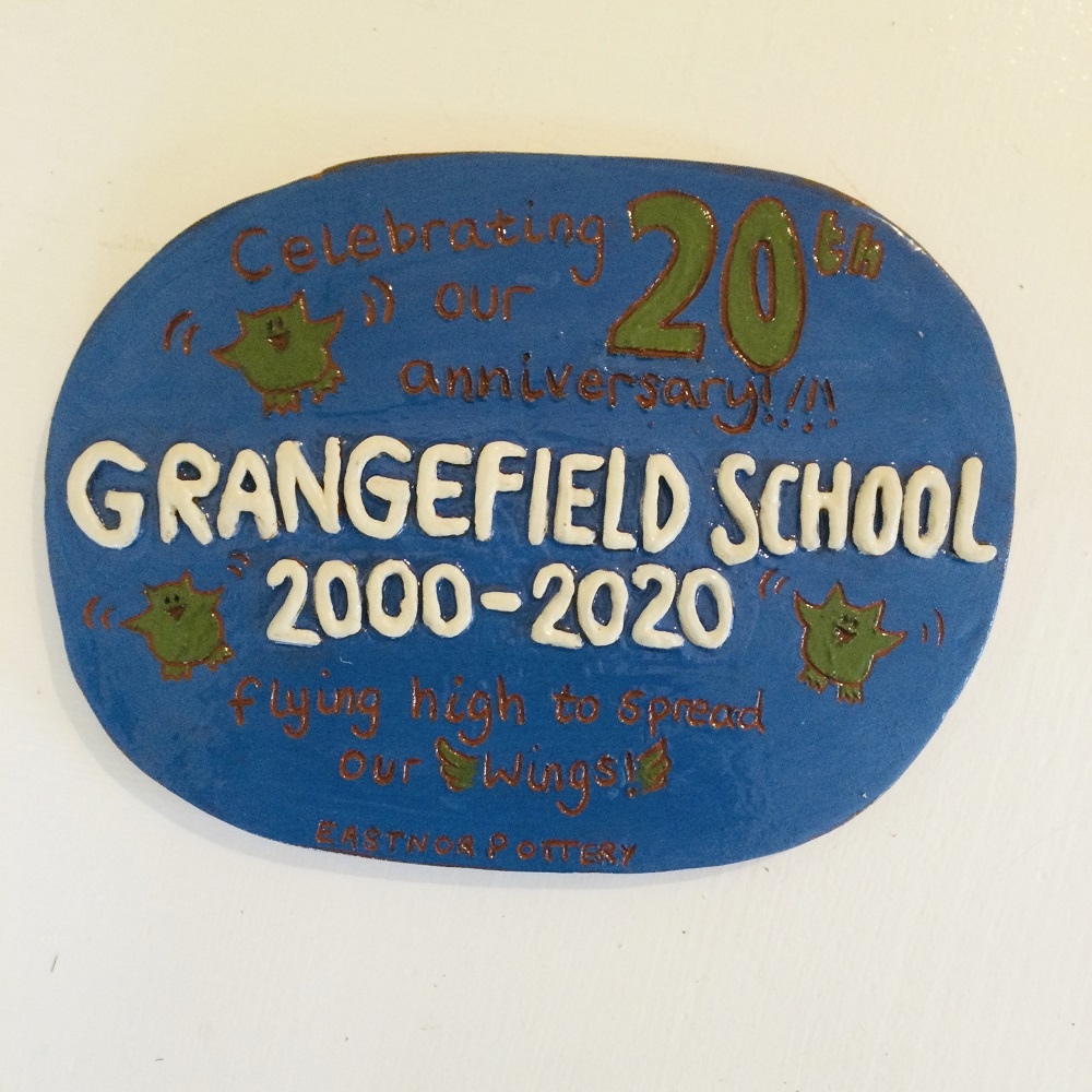 blue plaque with writing writing reading' grangefield school 2000-2020' and sgraffito writing reading 'celebrating our 20th anniversary, flying high to spread our wings, eastnor pottery'