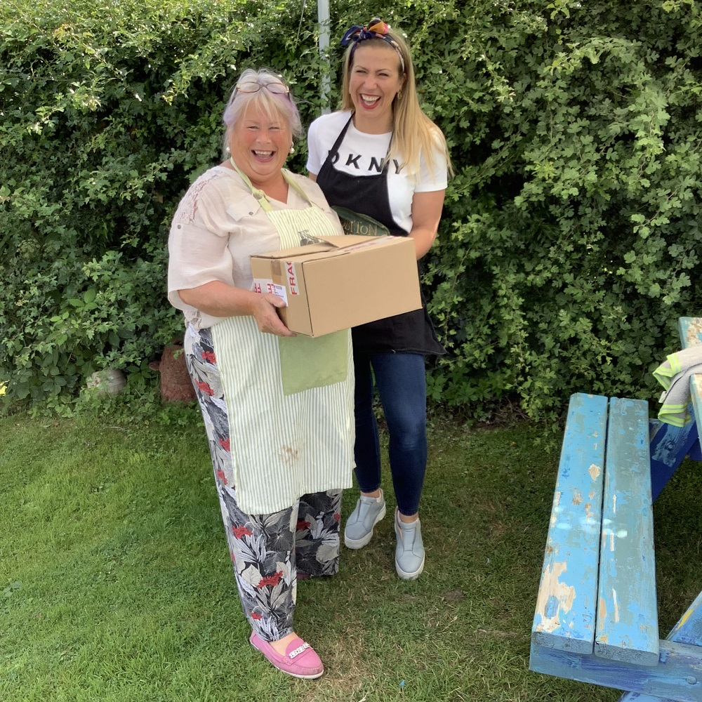 mother and daughter holding cardboard box smiling, in front of hedgerow