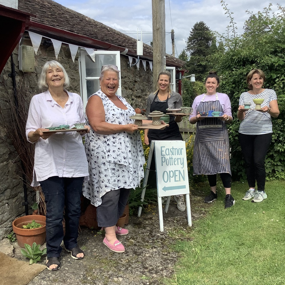 five women holding wodden boards with ceramic creations they have made standing outside eastnor pottery next to the eastnor pottery sign