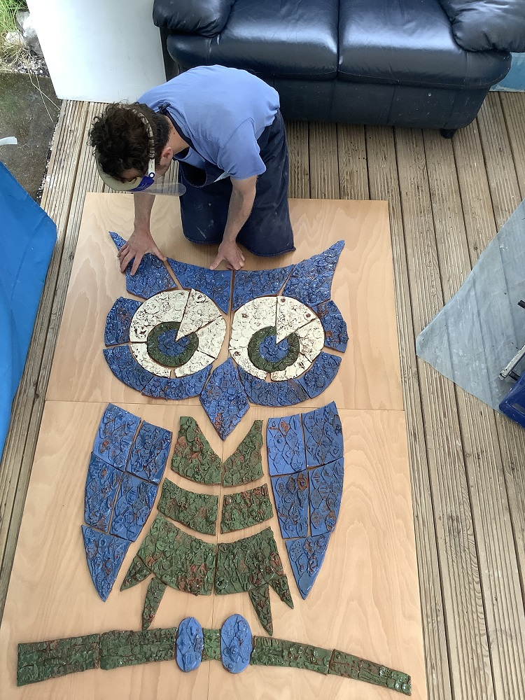 potter jon williams leaning over putting blue white and green tiles hand modeled with clay which together make up an owl
