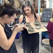 girls inspecting their fresh pots made on the potter's wheel at eastnor pottery