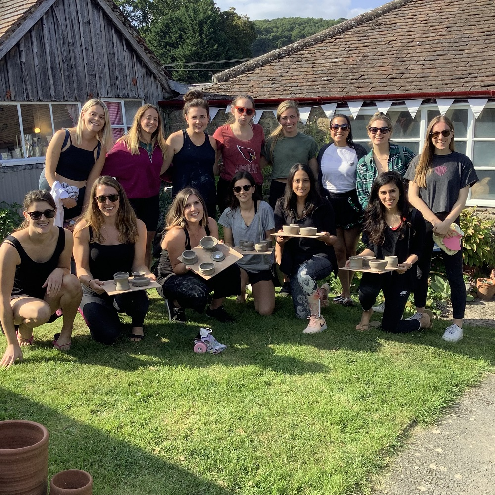 rosys hen party displaying their freshly thrown pots in the garden at eastnor pottery